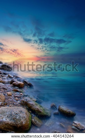 Later, sunless sea sunset with stones and a calm sea water. Natural landscape - stock photo