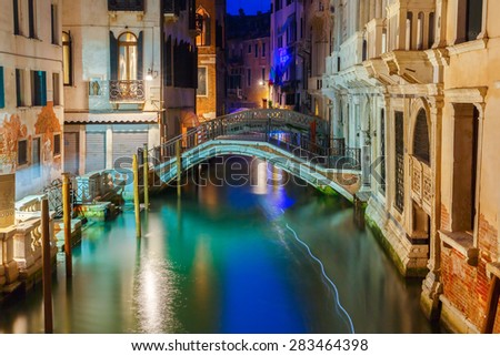Lateral canal and pedestrian bridge in Venice at night with street light illuminating bridge and houses, Italy