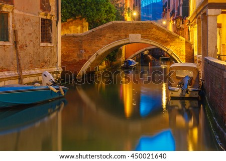 Lateral canal and pedestrian bridge in Venice at night with street light illuminating bridge and houses, with docked boats, Italy - stock photo