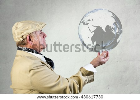 Lateral view of senior man with hat and neckerchief looking the world globe - stock photo