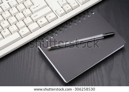 Laterally of stationery and computer keyboard on the black desk - stock photo