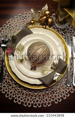 Latest trend of gold metallic theme Christmas  formal dinner table place setting with fine bone china, bauble and festive decorations. Vertical. - stock photo