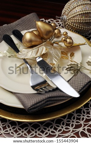 Latest trend of gold metallic theme Christmas  formal dinner table place setting with fine bone china, bauble and festive decorations. Close up on cutlery and plates - stock photo