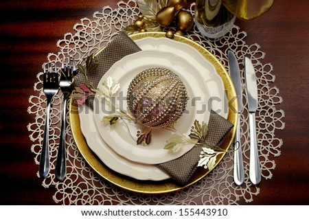 Latest trend of gold metallic theme Christmas  formal dinner table place setting with fine bone china, bauble and festive decorations. - stock photo