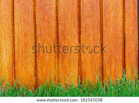 Lath wooden fence and green grass in the background. - stock photo