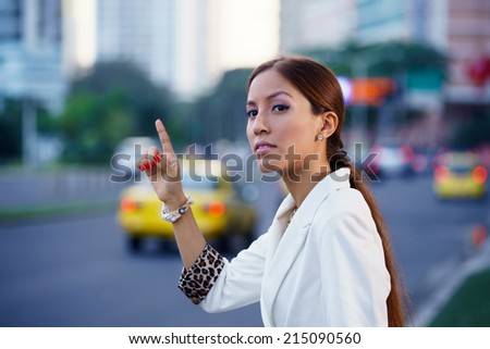 Latin american business woman standing in the street, calling yellow taxi after work - stock photo
