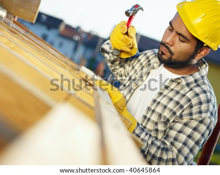 latin american construction worker on house roof with hammer. Copy space - stock photo