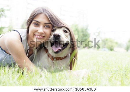 Latin American girl hugging her dog in the park on the background of the house