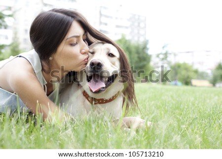 Latin American girl kissing her dog in the park on the background of the house - stock photo