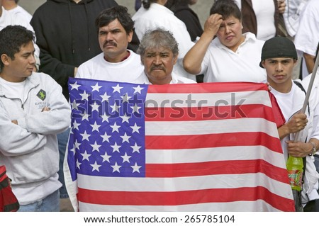 Latin American man holds US flag with hundreds of thousands of immigrants participating in march for Immigrants and Mexicans protesting against Illegal Immigration, Los Angeles, CA, May 1, 2006 - stock photo