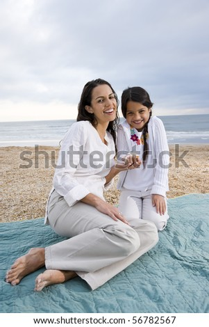 Latin American mother and 9 year old girl sitting on blanket at beach - stock photo