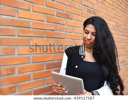 Latin beautiful woman using a tablet. Trendy and urban clothes.