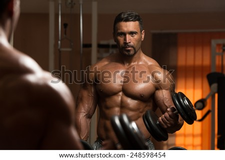 Latin Bodybuilder Working Out Biceps - Dumbbell Concentration Curls - stock photo