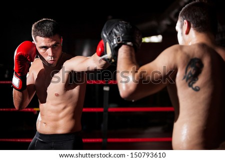 Latin boxer and his coach doing some sparring in the ring - stock photo