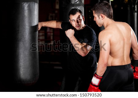 Latin Boxer and his coach practicing some moves on a punching bag at a gym - stock photo