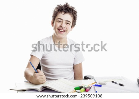 Latin Caucasian Teenager boy sitting while doing homework is happy and writing with pencil - stock photo