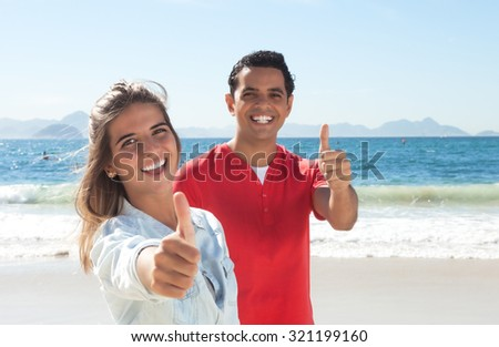 Latin couple at beach showing thumb up