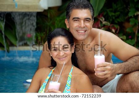 Latin couple drinking strawberry milkshake in a swimming pool. - stock photo