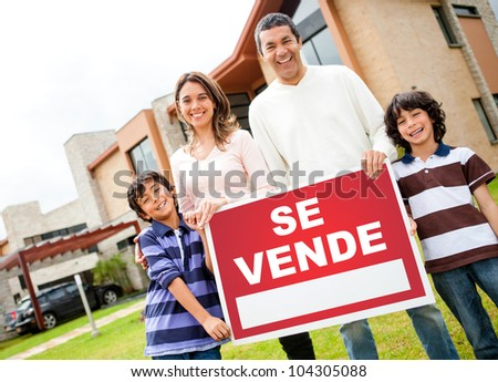 Latin family selling their house and holding a poster in spanish - stock photo