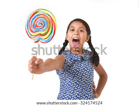 Latin female child holding huge lollipop sticking tongue out happy and excited in cute blue dress and pony tails standing isolated on white background in kid loving candy and sweet sugary food concept - stock photo