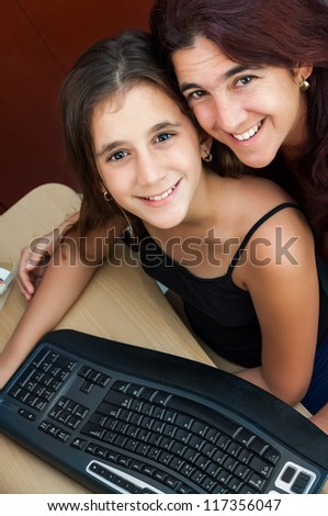 Latin girl and her beautiful mother working on a computer at home ( Image taken from above with the subjects smiling at the camera)