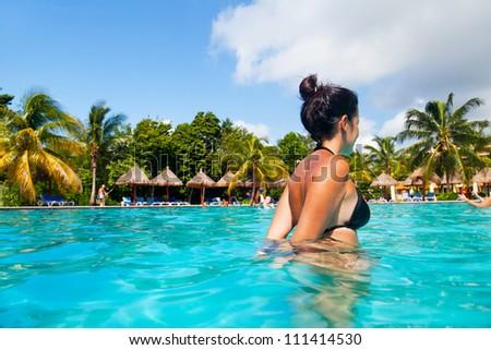 Latin Girl Having a Bath in a Tropical Pool - stock photo