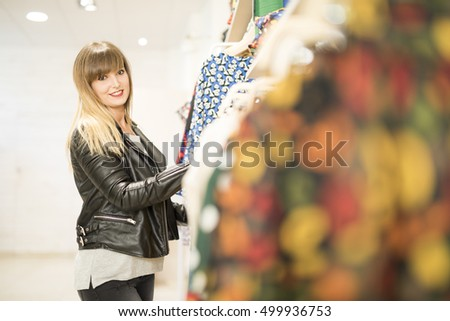 Latin girl in a lether jacket is choosing new clothes at the shop.