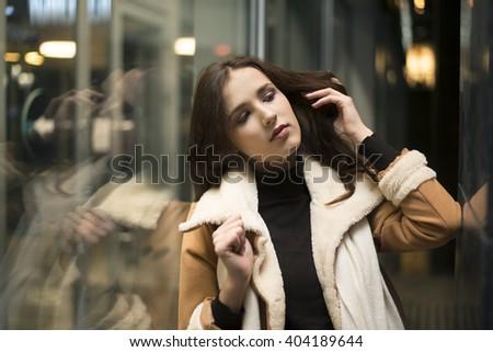 latin hispanic young adult woman stand near big shop window. Night scene. Brunette asian girl wear luxury coat with white fur. Evening shopping. - stock photo