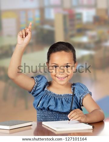 Latin little girl asking to speak at the school - stock photo