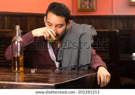 latin man in suit drinking alcohol shot finishing bottle