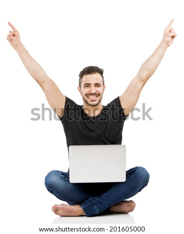 Latin man sitting on the floor and working with a laptop with both arms up