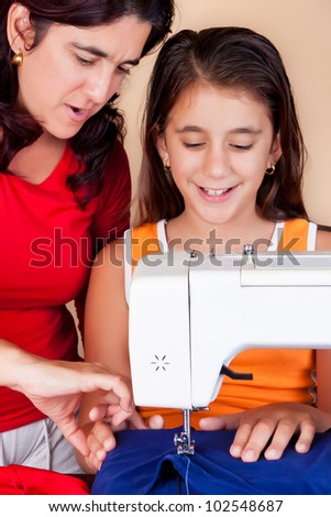 Latin  mother teaching her daughter how to use a sewing machine
