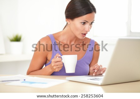 Latin shocked woman in purple shirt browsing the web on her laptop while holding a coffee mug at home