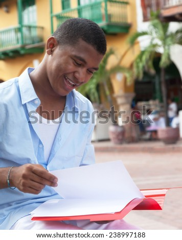 Latin student in a colonial town reading documents - stock photo