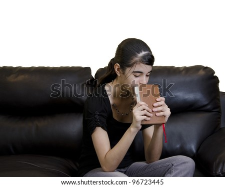 Latin teenager girl having a daily Christian devotional at home - stock photo