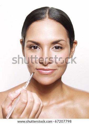 Latin woman aplying makeup powder on white background.   Latin woman applying blusher on white background. - stock photo