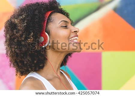 Latin woman listen music in the street