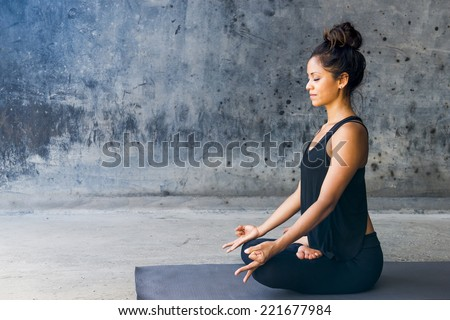Latin woman practicing meditation against a urban background - stock photo