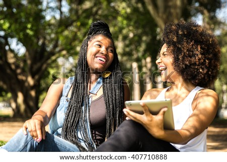 Latin women using tablet computer in the park - stock photo