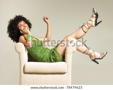 Latin young woman talking with telephone in a sofa. - stock photo