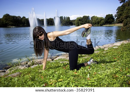 Latina is working out in the park stretching before a run