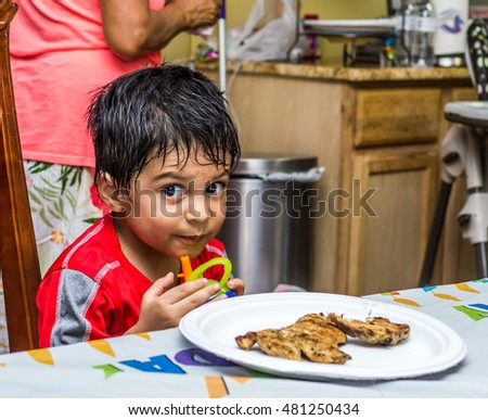 Latino child sitting at a table with food on a plate in front of him, holding a sippy cup and looking at the camera with a mischievous look on his face