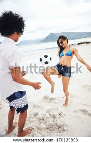 Latino couple playing soccer on beach with ball kicking and having fun - stock photo