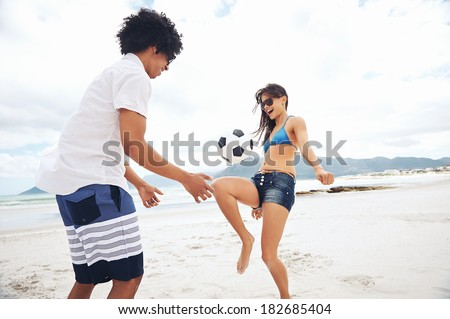 Latino couple playing soccer on beach with ball kicking and having fun