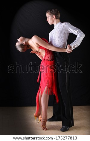 Latino dancers in ballroom against on blac