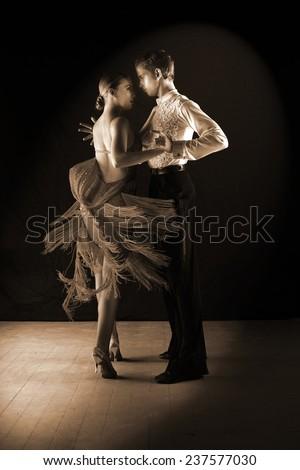 Latino dancers in ballroom against on black - stock photo