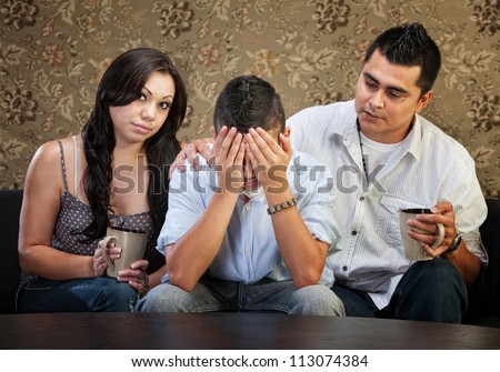 Latino parents comforting sad male teenager with hands in face - stock photo