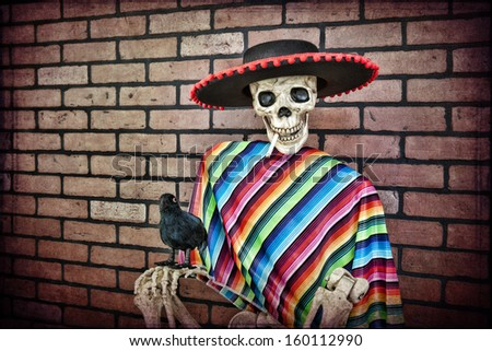 Latino skeleton sitting against a brick wall having a smoke with his trusty pet crow. - stock photo