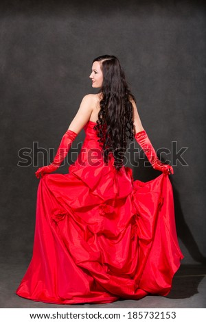 Latino Woman with long hair  in red waving dress dancing  in action with flying fabric on dark grey background