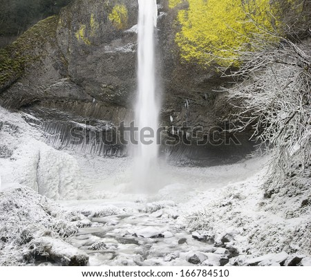 Latourell Falls at Columbia River Gorge Oregon with Icicles and Flowing Stream Frozen in Winter Season - stock photo